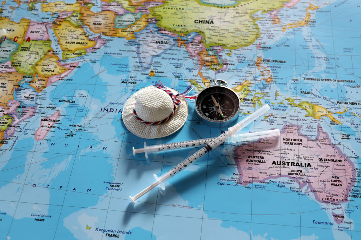 A compass with two disposable syringes and travel cap on world map.